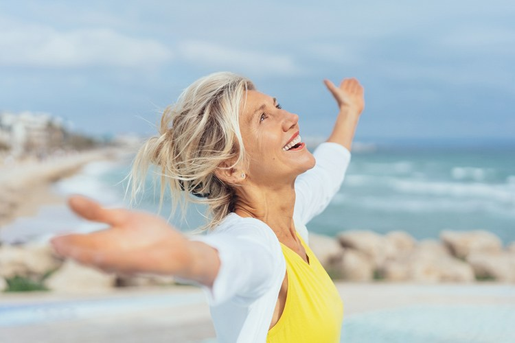 Woman stretching her arms out, outside, happy